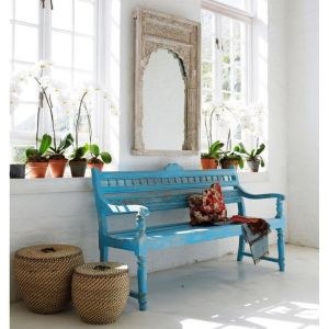 A rustic blue Indian bench adds a splash of calming colour to a neutral interior.