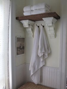 Ornate wooden brackets support a thick wooden shelf.
